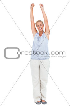 Excited woman standing with arms raised