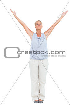 Blonde woman standing with arms outstretched