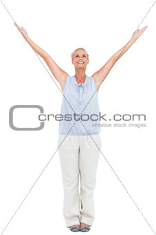 Blonde woman standing with hands up in air