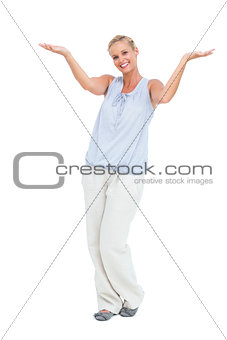Blonde woman with arms raised smiling at camera