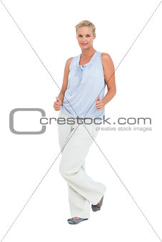 Blonde woman standing with thumbs up at her hips