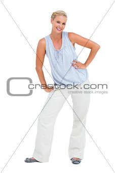 Blonde woman smiling at camera and bending with hands on hips