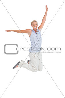 Blonde woman jumping with hands up in air