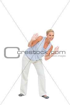 Blonde woman bending down with hands up