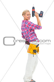 Blonde woman standing holding a drill