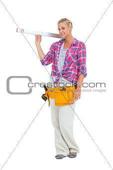 Blonde woman standing while holding a spirit level