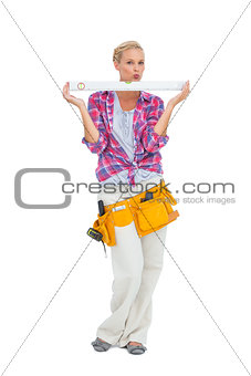 Blonde woman standing holding a spirit level