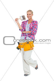 Blonde standing while holding a paint brush