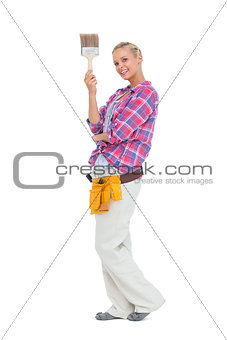 Blonde standing holding paint brush