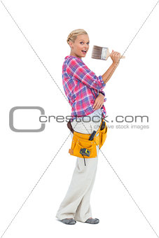 Blonde holding paint brush wearing a tool belt