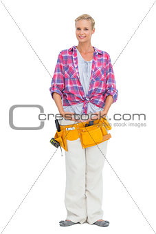 Smiling woman wearing a tool belt in ballerina pose
