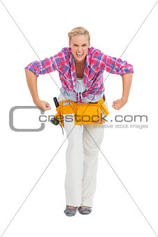 Blonde woman tensing arms wearing tool belt