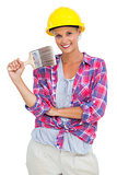 Attractive handy woman holding a brush and smiling at camera
