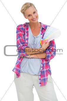 Attractive young woman smiling at camera holding colour charts
