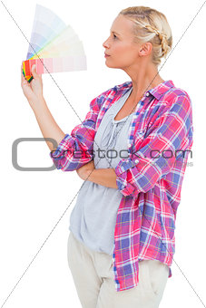 Blonde looking at colour charts and picking colour