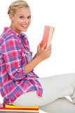Happy woman sitting on a stack of books and holding a book