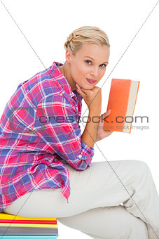 Attractive young woman holding a book and sitting on a stack of books