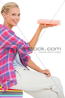 Beautiful woman showing a book and smiling at camera