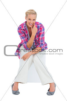 Attractive young woman sitting and smiling at camera