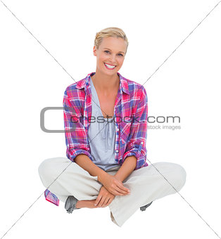 Beautiful blonde sitting on the floor and smiling at camera