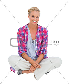 Attractive blonde sitting on the floor and smiling