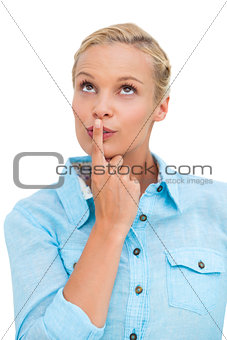 Blonde woman standing with her finger on her lips