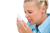 Ill woman sneezing into tissue