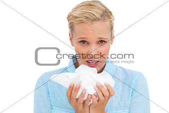 Blonde sick woman holding lots of tissues