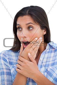 Astonished young woman with hands on chin