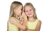 Blonde girl whispering to her sister