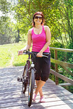 pretty woman with bicycle on small wooden bridge