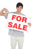 Smiling man pointing at for sale sign