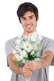 Young man offering a flower bouquet