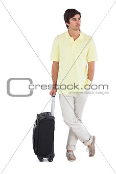 Serious man standing with his suitcase
