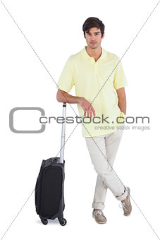 Calm man standing with his suitcase