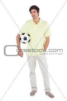 Serious man holding soccer ball