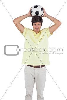Man holding soccer ball behind his head