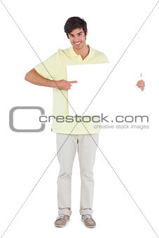 Smiling man pointing something on empty sign