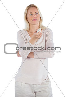 Thoughtful woman with remote control