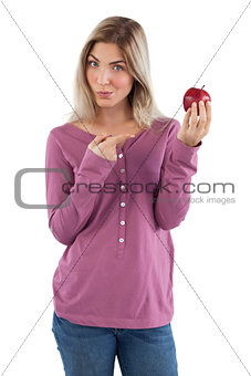 Blonde woman pointing to apple with her finger