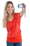 Smiling blonde woman taking picture of herself