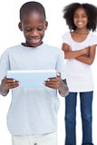 Little boy looking at a tablet pc with his sister