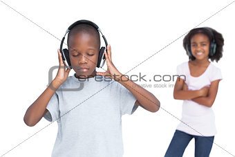 Little boy with eyes closed listening to music with his sister