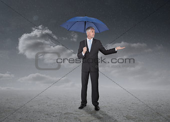 Businessman holding a blue umbrella