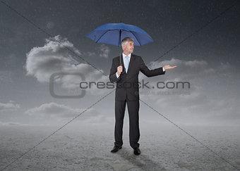 Businessman holding a blue umbrella