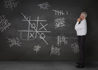 Doubtful businessman looking at tic-tac-toe