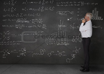 Elegant businessman looking at maths equations