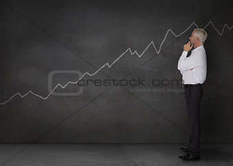 Well dressed businessman looking at a white chart
