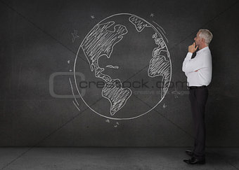 Thoughtful businessman looking at an earth drawn with a chalk