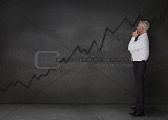 Well dressed businessman looking at a black chart